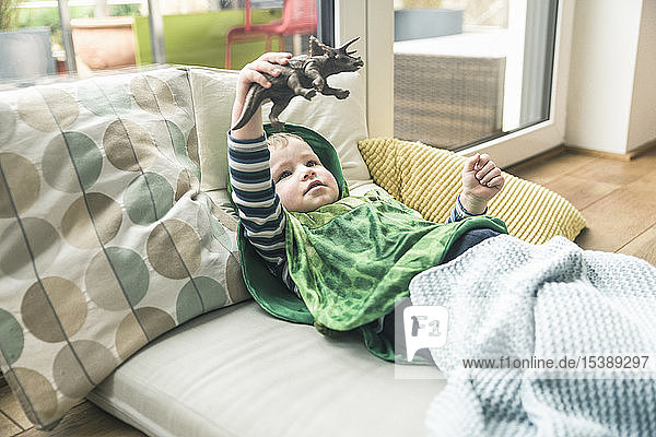 Boy in a costume lying on amattress playing with toy figure at home