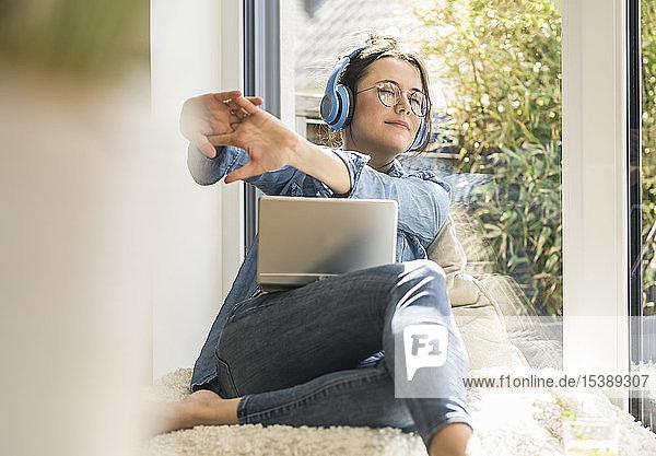 Frau mit Kopfhörern und Laptop  die zu Hause am Fenster sitzt