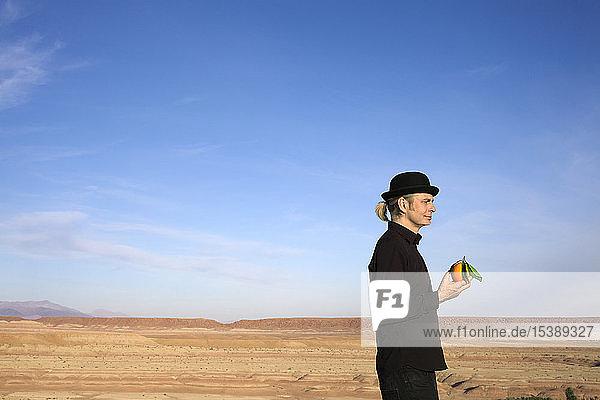 Morocco  Ounila Valley  man wearing a bowler hat holding an orange