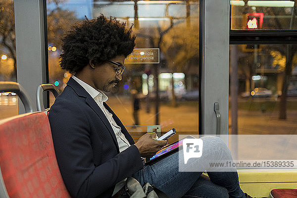 Spain  Barcelona  businessman in a tram at night using cell phone and tablet