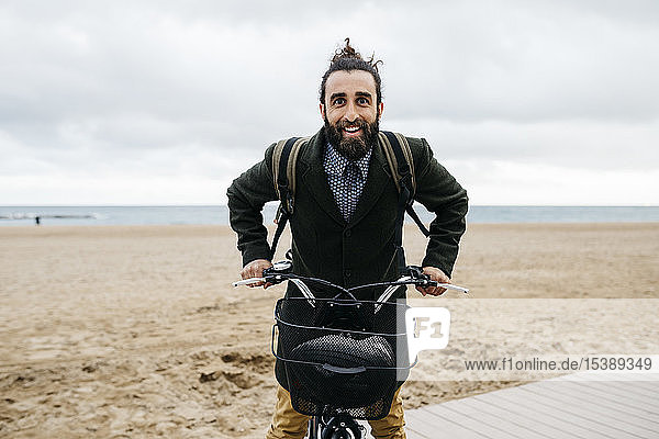 Portrait of happy man with e-bike at the beach
