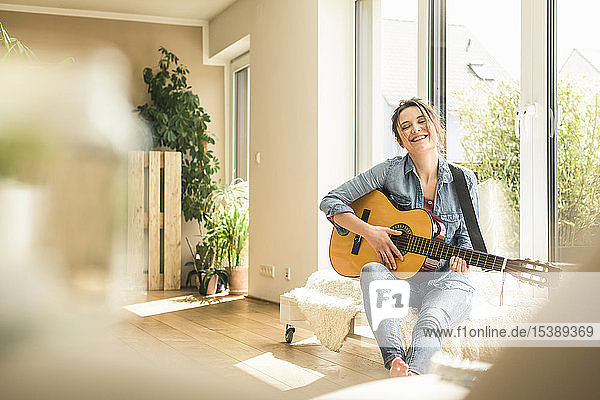 Happy woman sitting at the window at home playing guitar