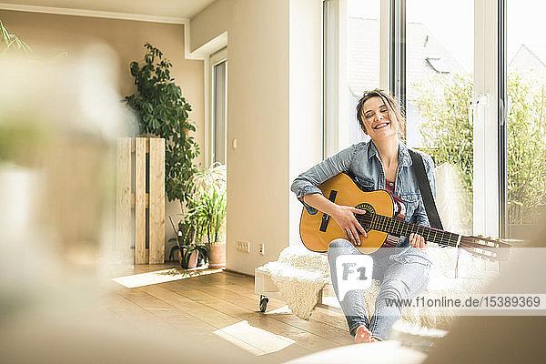 Glückliche Frau sitzt zu Hause am Fenster und spielt Gitarre