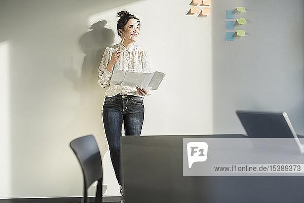 Lächelnde Geschäftsfrau hält Plan im Amt