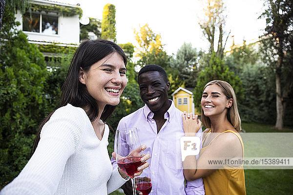 Freunde amüsieren sich bei einem sommerlichen Abendessen im Garten und nehmen sich selbst