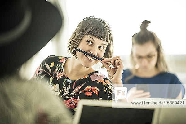 Colleagues having fun in office  making fun with a pencil moustache