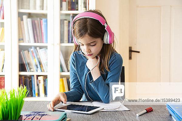 Kleines Mädchen macht Hausaufgaben mit Kopfhörer und digitalem Tablet