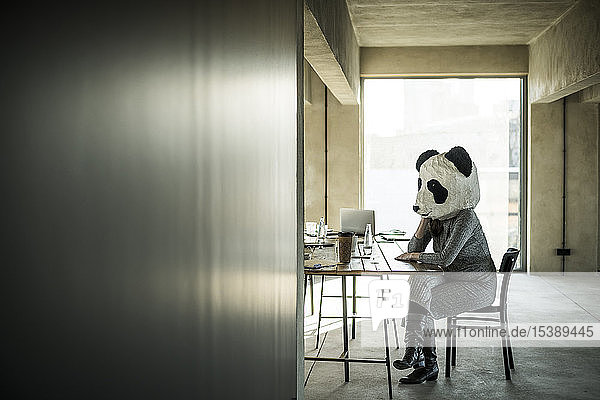 Woman with panda mask sitting in office  thinking