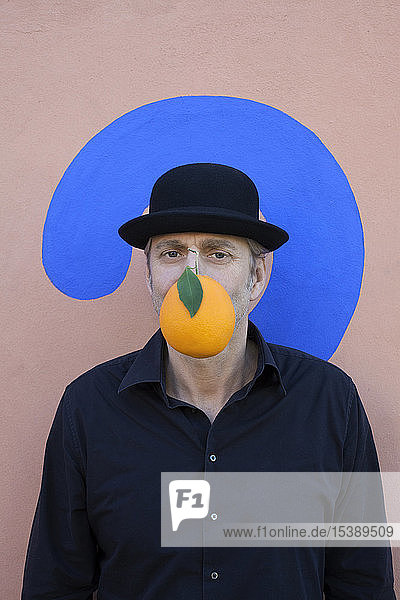 Portrait of man with an orange at a wall with question mark wearing a bowler hat