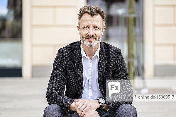Porträt eines lächelnden reifen Geschäftsmannes mit grauem Bart im Freien
