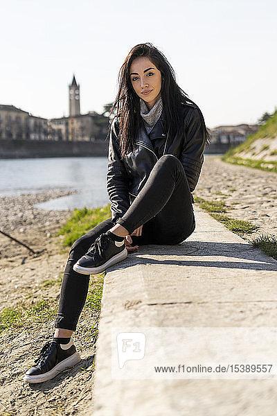 Italien  Verona  Porträt einer jungen Frau  die am Flussufer sitzt