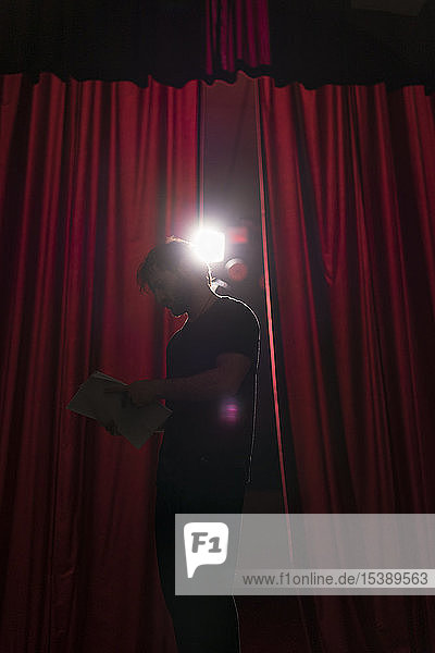 Schauspieler  der auf der Bühne des Theaters steht und das Drehbuch studiert