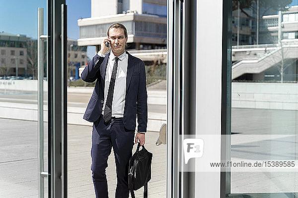 Italien  Florenz  junger Geschäftsmann auf Smartphone im Freien