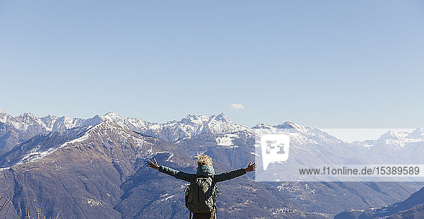 Italien  Como  Frau auf einer Wanderung in den Bergen  die die Aussicht genießt