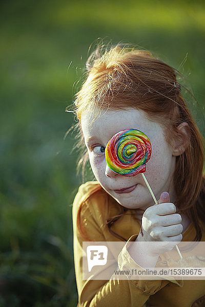 Grimacing girl covering her eye with a lollipop