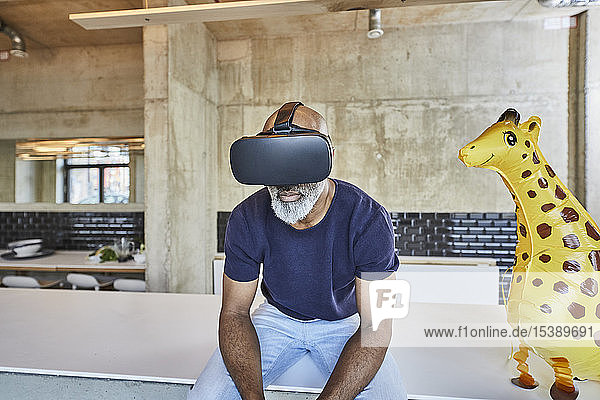 Mature businessman in modern office sitting next to giraffe figurine wearing VR glasses
