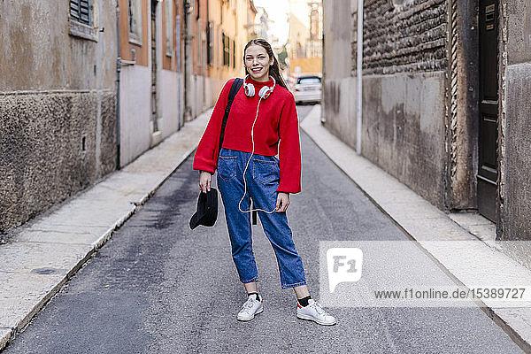 Junge Frau mit rotem Pullover und Kopfhörern in Verona