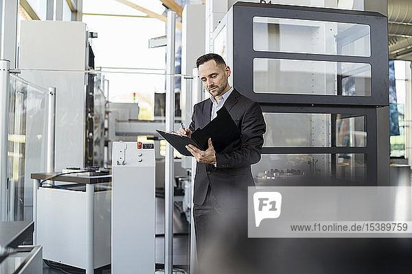 Geschäftsmann betrachtet Ordner in moderner Fabrik
