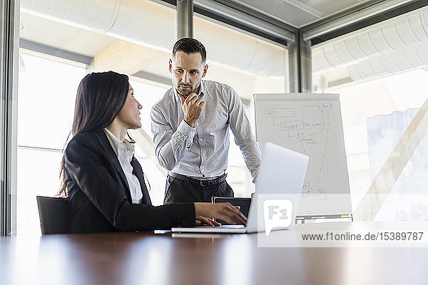 Businessman and businesswoman with laptop working in office