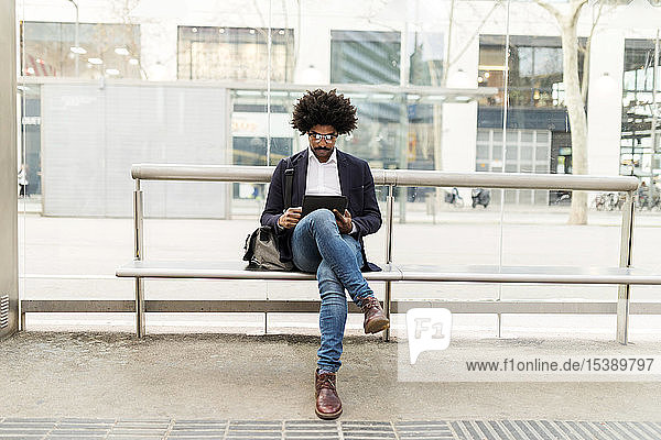 Spain  Barcelona  businessman in the city sitting on bench at a station using tablet
