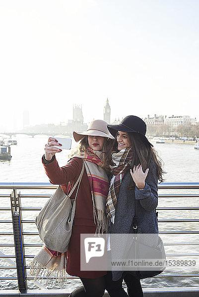 UK  London  two women taking a selfie on Millennium Bridge with cityscape in background