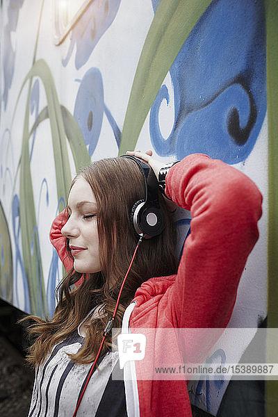 Portrait of teenage girl wearing headphones at a painted train car