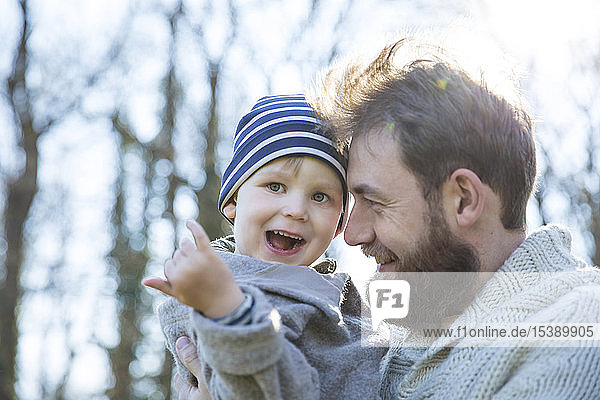 Glücklicher Vater trägt Sohn im Park