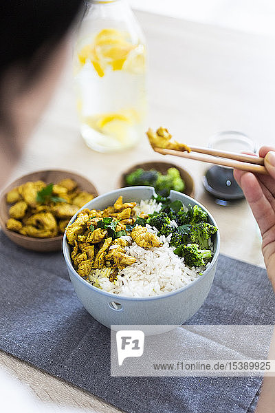 Curry-Huhn  Brokkoli und Reis  Frau isst mit Stäbchen