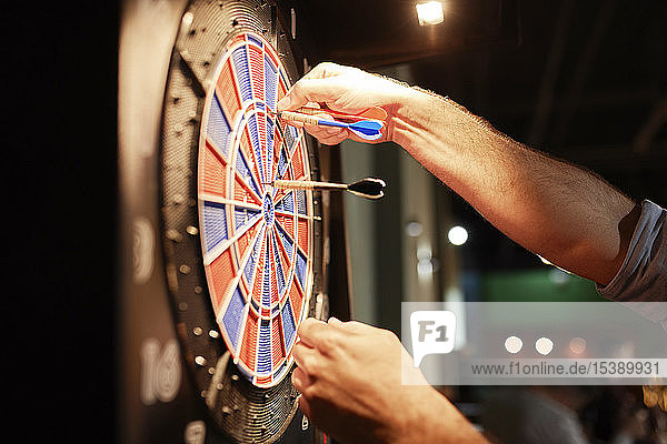 Close-up of man taking out darts from electronic dartboard