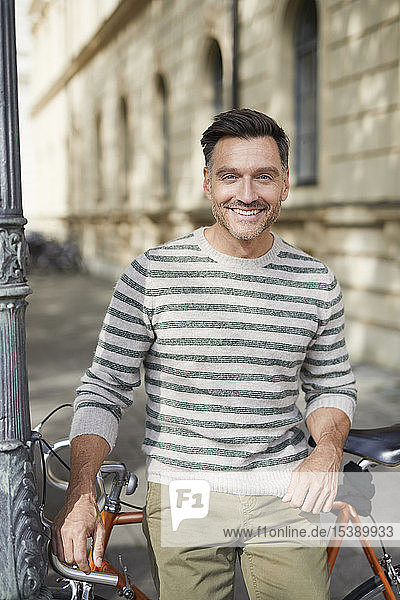 Portrait of smiling man with bicycle in the city