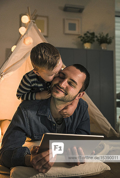 Son kissing father with tablet at an illuminated tent at home