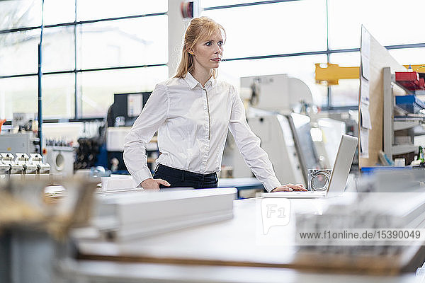 Geschäftsfrau mit Laptop in der Fabrik
