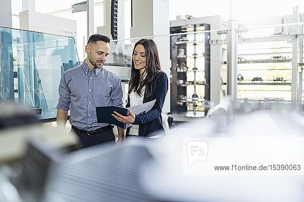 Lächelnder Geschäftsmann und Geschäftsfrau betrachten Ordner in moderner Fabrik