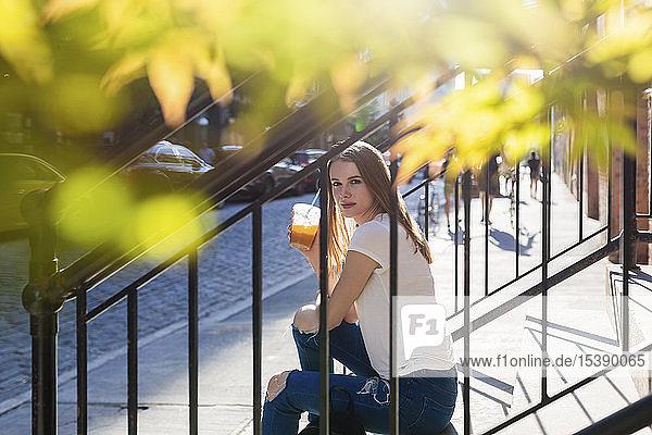 Junge Frau erkundet New York City  sitzt auf einer Treppe und trinkt Kaffee