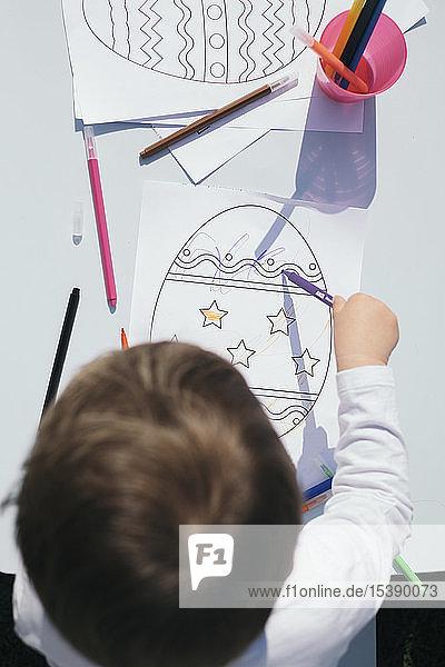 Draufsicht eines Kleinkindes beim Ausmalen eines Ostereies auf einem Papier