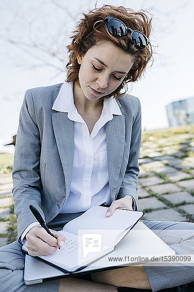 Businesswoman in the city  sitting on ground  writing in notebook