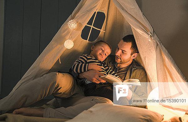 Vater liest dem Sohn in einem beleuchteten Zelt zu Hause ein Buch vor