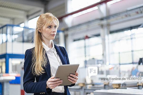 Geschäftsfrau hält Tablette in der Fabrik