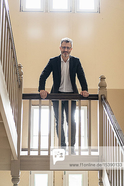 Portrait of smiling businessman standing in the stairwell