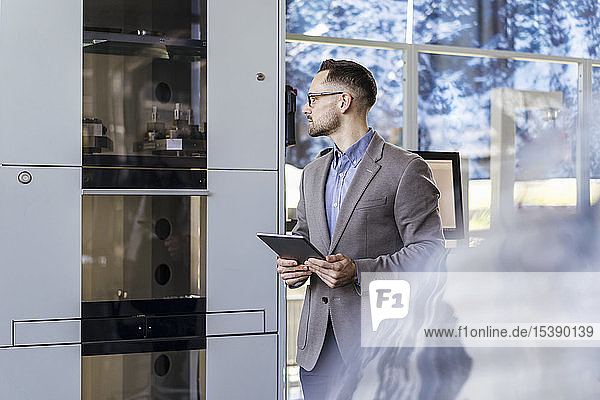 Businessman with tablet looking at machine in a modern factory