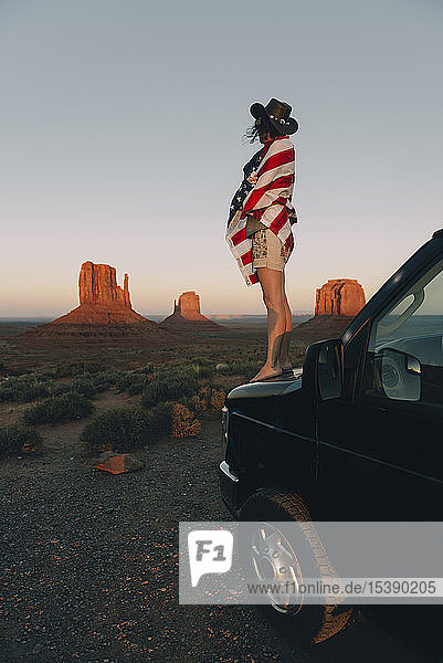 USA  Utah  Monument Valley  Woman with United States of America flag enjoying the sunset in Monument Valley
