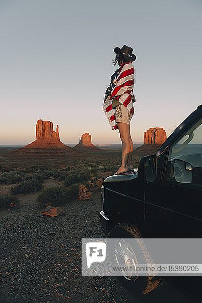 USA  Utah  Monument Valley  Frau mit der Flagge der Vereinigten Staaten von Amerika genießt den Sonnenuntergang im Monument Valley
