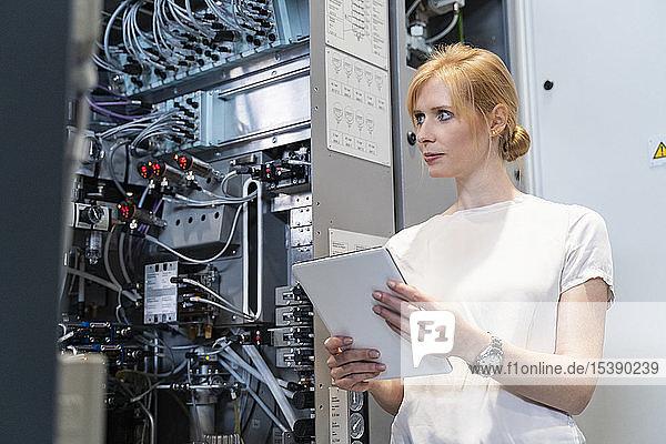 Geschäftsfrau mit Tablette an Maschine in Fabrik