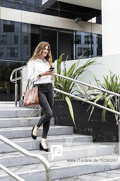 Junge Geschäftsfrau geht die Treppe hinunter und benutzt ein Smartphone