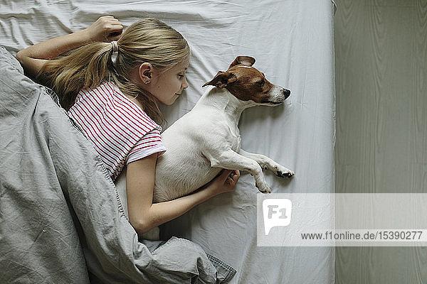 Blondes Mädchen im Bett liegend  ihr Hund schläft  Draufsicht