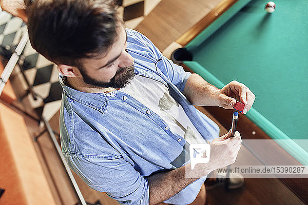 Man preparing his billiards cue
