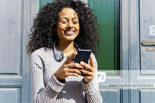 Lachende Frau mit Smartphone in der Hand