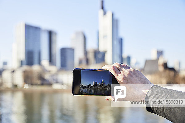 Germany  Frankfurt  hand taking photo of financial district with cell phone