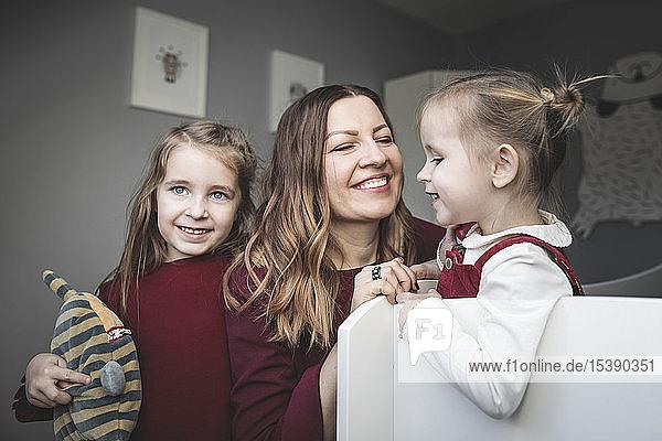 Glückliche Mutter mit zwei Mädchen zu Hause