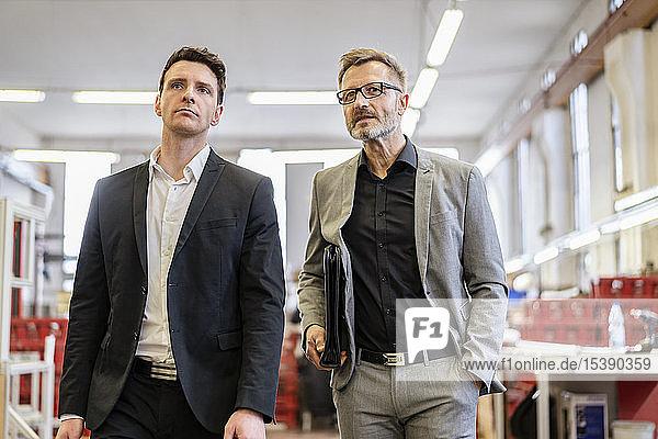 Zwei Geschäftsleute zu Fuß in einer Fabrik
